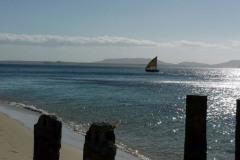 Loďka plující k dřevěnému molu uprostřed vesnice Ramena.